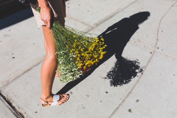 Young Woman with Bunch of Flowers Using a Mobile Phone on the Street