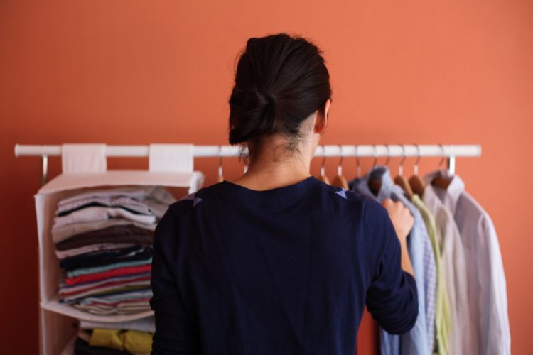 Woman choosing shirt in her room