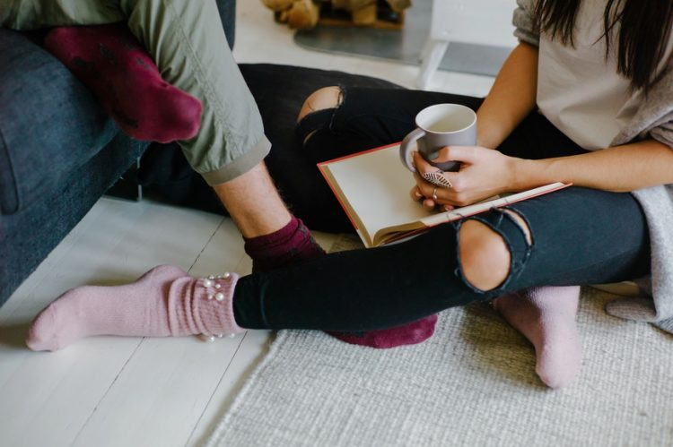 Crop shot of woman with hot tea and book chilling with boyfriend sitting on floor and cuddling.